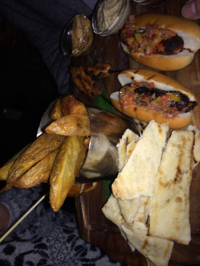 Yummy food platters of potato wedges, hot dogs, pitta bread and dips